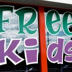 "Painted sign in store window that says ""Free Kids"""